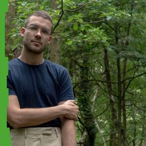 Photo of Jaka Skapin, standing, in front of greenery/forest.